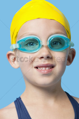 Swimmer : Close-up portrait of a happy young girl wearing swim cap and goggles over blue background