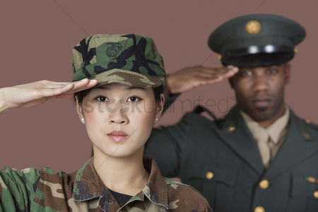 Respect : Close-up portrait of young female us marine corps soldier with male officer saluting over brown background