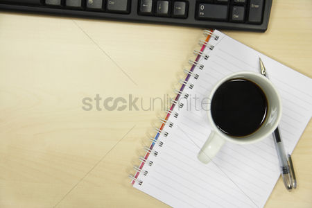 Notebook : Coffee mug and pen on desk by computer overhead view close up