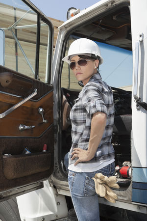 Land : Confident female industrial worker standing by vehicle door with hand on hip