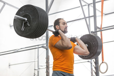 Muscle training : Confident man looking away while lifting barbell in crossfit gym