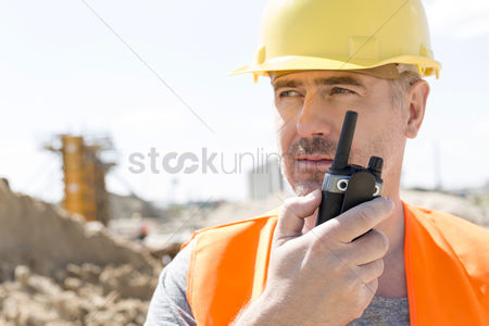 Supervisor : Confident supervisor using walkie-talkie at construction site