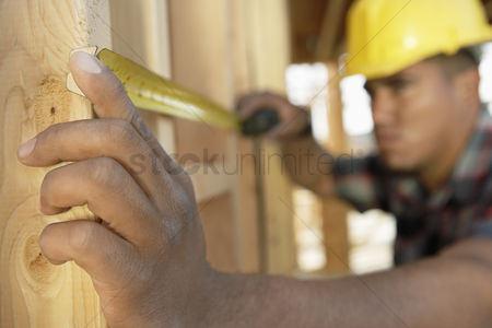 Hispanic : Construction worker measuring between boards with tape measure on construction site