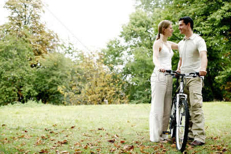 Relationship : Couple and a bicycle in the park
