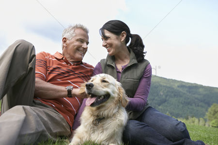 Appearance : Couple and golden retriever resting on grass