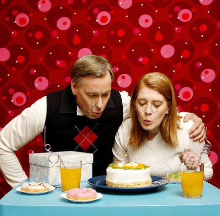 Birthday present : Couple blowing candle on the birthday cake