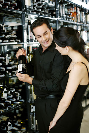 Advice : Couple choosing wine at wine cellar