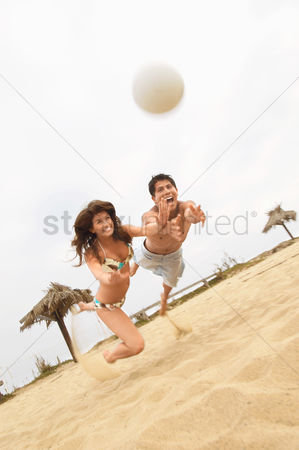Diving : Couple diving for volleyball on beach tilt view