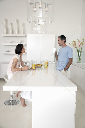 White hair : Couple eating breakfast at kitchen bench side view