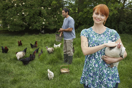 Large group of animals : Couple feeding hens in garden portrait