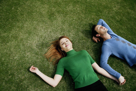 Two people : Couple holding hands while lying on the field