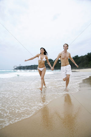 Refreshment : Couple holding hands while running on the beach