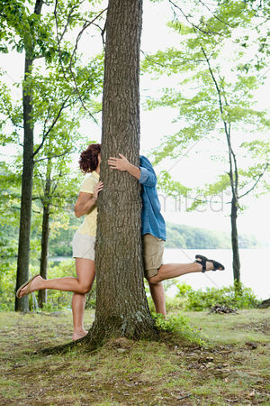 Kissing : Couple kissing behind a tree