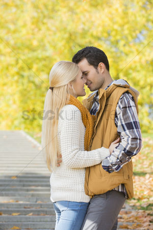 Jacket : Couple kissing in park during autumn