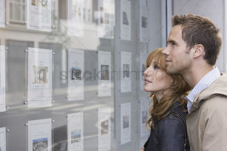 Contemplation : Couple looking in window outside estate agents