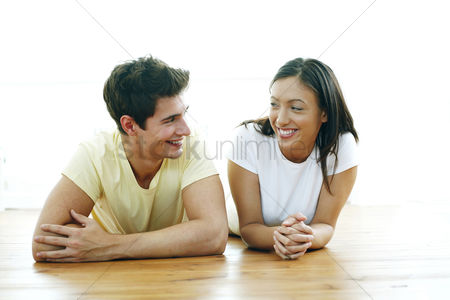 Couples : Couple lying forward on the floor smiling at each other