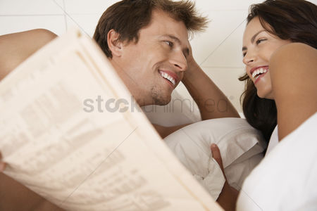 Day off : Couple lying in bed reading newspaper head and shoulders