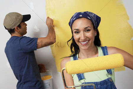 Arts : Couple painting interior wall yellow