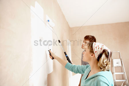 Interior : Couple painting wall with paint rollers indoors