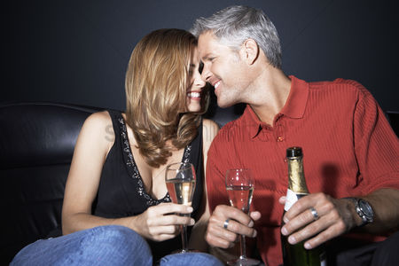 Toasting : Couple sitting rubbing noses holding champagne glasses