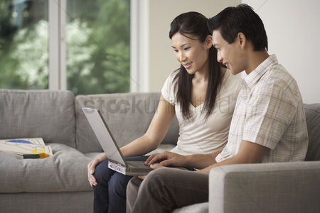 Young woman : Couple sitting side by side on sofa using a laptop