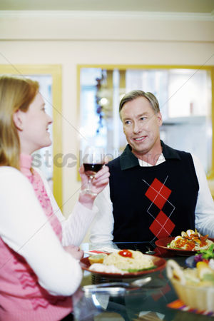 Having fun : Couple talking while eating at the dining table