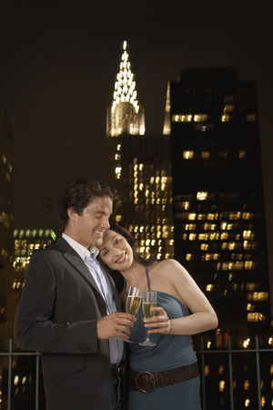 Attraction : Couple toasting with champagne against new york night skyline