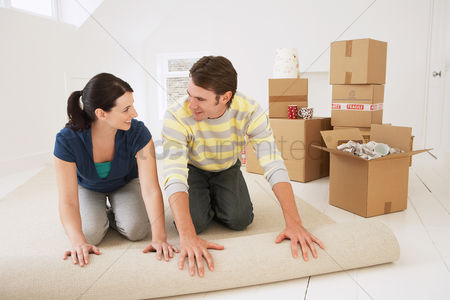 Interior : Couple unrolling carpet in new home