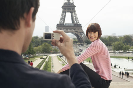 Couples : Couple using camera phone and eiffel tower