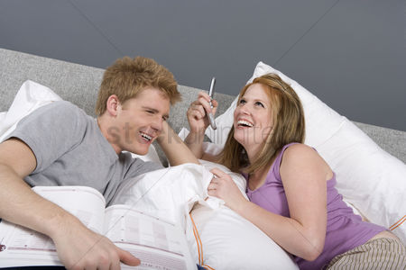 Cellular phone : Couple using cell phone together bedroom