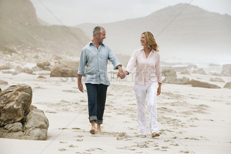 Mature : Couple walking on beach holding hands