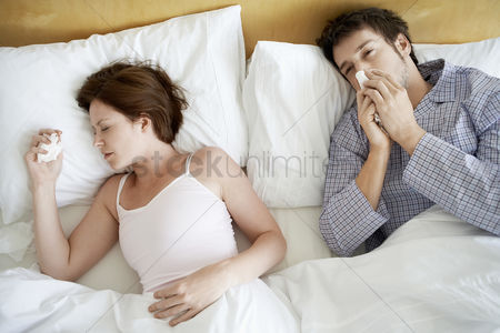 Cold : Couple with colds lying in bed high angle view