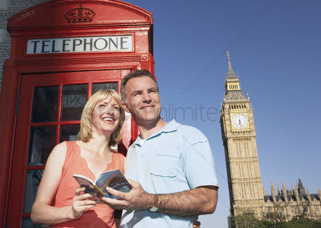 England : Couple with guidebook standing by london phone booth