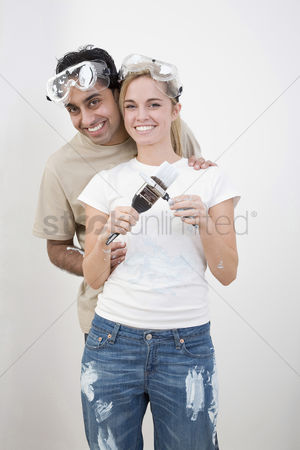 Paint brush : Couple with protection goggles and paint brush posing for the camera