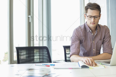 Women : Creative businessman reading file at desk in office