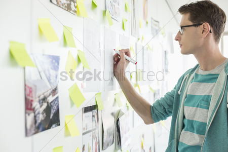 Women : Creative businessman writing on paper in office