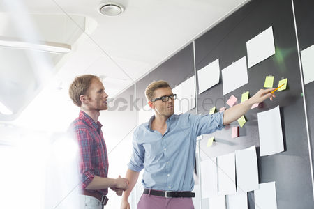 Two people : Creative businessmen discussing over sticky paper on wall in office