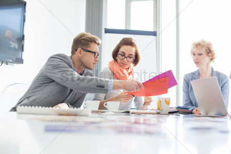 Creativity : Creative businesspeople analyzing documents at desk in office