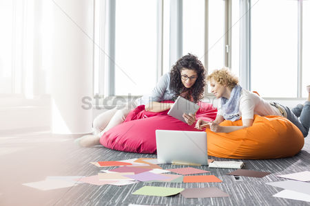 Creativity : Creative businesswomen using tablet pc while relaxing on beanbag chairs at office