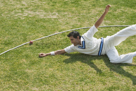 Diving : Cricket fielder diving to stop a ball near boundary line