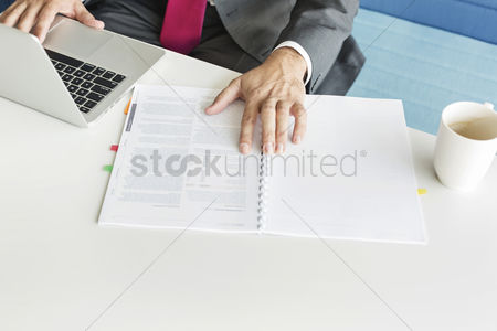 Businessmen : Cropped image of businessman with book and laptop at desk