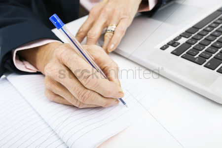 Notebook : Cropped image of businesswoman with laptop writing in book on office desk