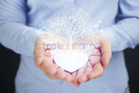 Conceptual : Cupped hands with tree of life in a heart