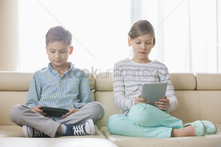 Pre teen : Cute siblings using technologies on sofa at home
