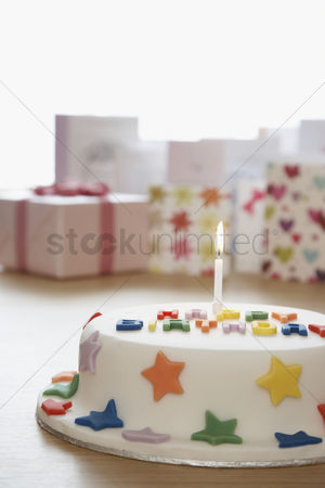 Shape : Decorated birthday cake with candle in front of cards in studio
