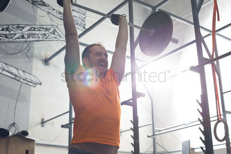 Muscle training : Dedicated man lifting barbell in crossfit gym