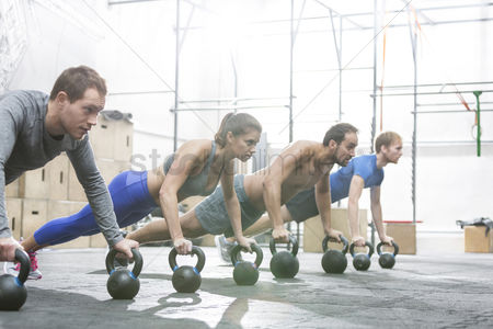Women : Dedicated people doing pushups with kettlebells at crossfit gym