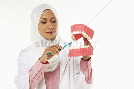 Tooth brush : Dentist demonstrating how to brush teeth