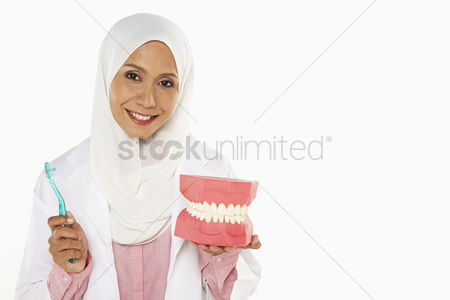 Tooth brush : Dentist holding a tooth brush and artificial dentures