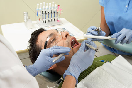 Examination : Dentists examining male patient in surgery  close-up
